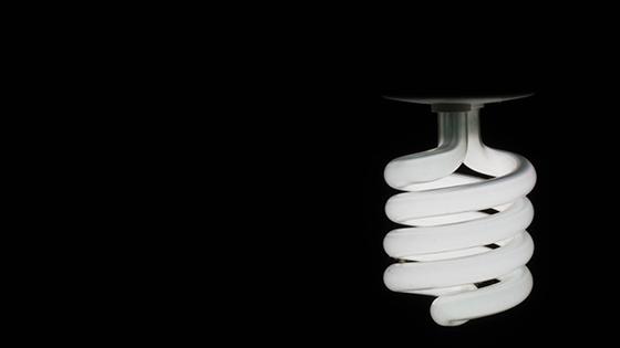 Energiesparlampe vor schwarzem Hintergrund